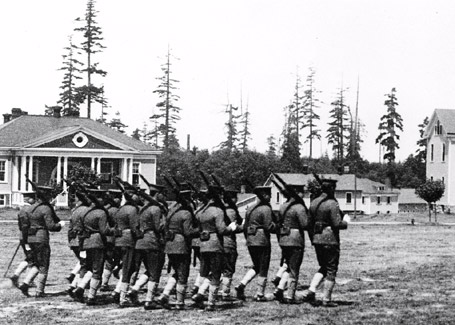 A squad of troops marching past the Post Exchange and Gymnasium  on the Fort Lawton parade ground. These soldiers are wearing the  standard service uniform issued circa 1903. Photo by Asahel Curtis.  Seattle Department of Parks and Recreation, Discovery Park Photographic  Archive, Photographer's File #U-3, a portion of 14734. Circa 1909.