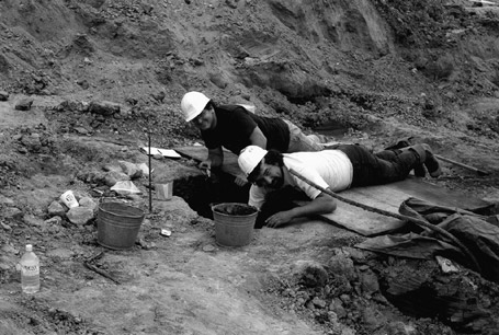 Leonard Forsman, right, a young man at the time (and, in later years to become the Chief of the Suquamish tribe) and a fellow worker examining a section of the 1992 dig site at West Point. Courtesy of King County. Collection held in trust at the Burke Museum, Seattle. 1992.