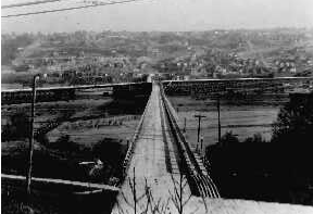 This 1929 photo shows the 23rd Avenue West Trestle from the left (north) and the Garfield Street Trestle from the right (east) meeting at mid-point. This route to Magnolia was about to end when the concrete Garfield Street Bridge replaced the wooden trestle during the next seven months. Seattle Municipal Archives #29360.