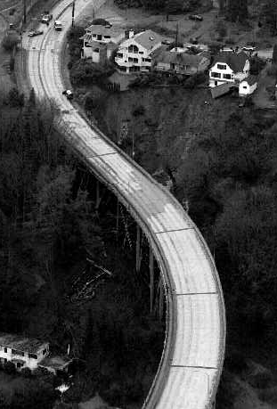 The January 1997 mudslide swept down the hill between two of the bridge's support columns, knocking out cross braces and filling the navy home below the bridge with debris. Courtesy of The Seattle Times.